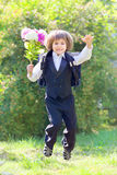 Schoolboy in uniform with a bouquet jumps. Schoolboy in uniform with a bouquet and satchel jumping in garden Stock Photo