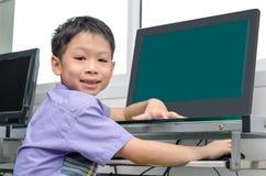 Schoolboy using computer Stock Image