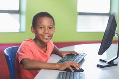 Schoolboy using computer in classroom. Portrait of schoolboy using computer in classroom at school Stock Photography