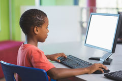Schoolboy using computer in classroom Royalty Free Stock Photography