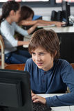 Schoolboy Using Computer At Desk. Little schoolboy using computer at desk with classmates in background Royalty Free Stock Photos