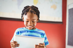 Schoolboy using digital tablet in classroom Royalty Free Stock Images