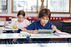 Schoolboy Using Digital Tablet In Classroom Royalty Free Stock Photography