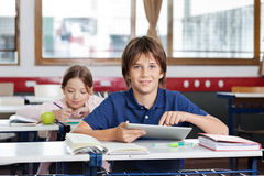 Schoolboy Using Digital Tablet In Classroom. Portrait of cute schoolboy using digital tablet with schoolgirl in background at classroom Royalty Free Stock Photos