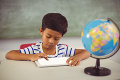 Schoolboy using digital tablet in classroom. At school Royalty Free Stock Photo