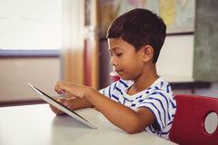 Schoolboy using digital tablet in classroom. At school Royalty Free Stock Photography