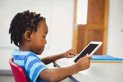 Schoolboy using digital tablet in classroom Royalty Free Stock Photos