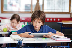 Schoolboy Using Digital Tablet At Desk. Elementary schoolboy using digital tablet with classmate studying in background at classroom Stock Images