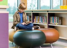 Schoolboy Using Digital Tablet In Library Royalty Free Stock Image