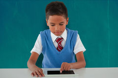 Composite image of schoolboy using digital tablet at table Royalty Free Stock Images