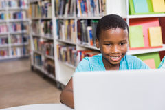 Schoolboy using laptop in library Stock Photography