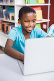 Schoolboy using laptop in library. At school Stock Image