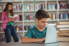 Schoolboy using laptop in library Royalty Free Stock Photo