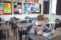 Schoolboy using laptop and mobile phone on desk. At classroom Royalty Free Stock Photography