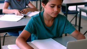 Schoolboy using laptop while studying in classroom. At school stock video footage