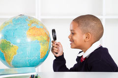 Schoolboy using magnifying glass Royalty Free Stock Images
