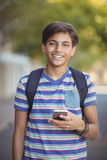 Schoolboy using mobile phone in campus at school Royalty Free Stock Photo