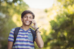 Schoolboy using mobile phone in campus at school Stock Photos