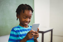 Schoolboy using mobile phone in classroom Stock Images