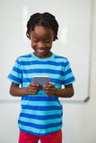 Schoolboy using mobile phone in classroom Stock Photo