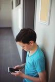 Schoolboy using mobile phone in corridor at school Stock Image