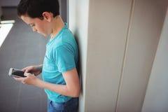 Schoolboy using mobile phone in corridor at school Stock Photos