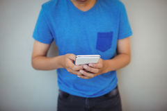 Schoolboy using mobile phone in corridor at school Royalty Free Stock Photo