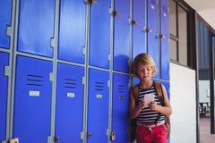Schoolboy using mobile phone while standing by lockers Stock Images