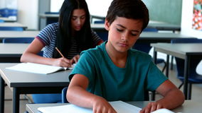 Schoolboy using mobile phone while studying in classroom. At school stock video footage