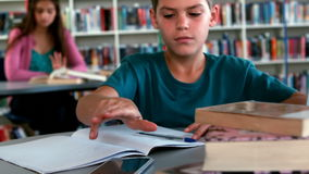 Schoolboy using mobile phone while studying in library. At school stock video