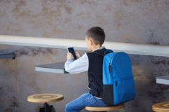 Schoolboy using smartphone in cafe Stock Image