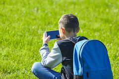 Schoolboy using smartphone on a green lawn. School playground Stock Photo