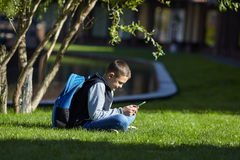 Schoolboy using smartphone on a green lawn. School playground Royalty Free Stock Images