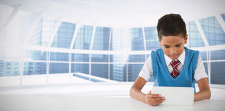 Composite image of schoolboy using tablet at table Stock Images