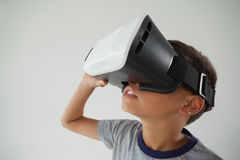 Schoolboy using virtual reality headset. Against white background royalty free stock photos