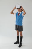 Schoolboy using virtual reality headset. Against white background Stock Image