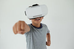 Schoolboy using virtual reality headset. Against white background Royalty Free Stock Images