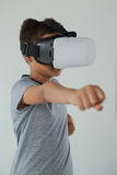 Schoolboy using virtual reality headset. Against white background Royalty Free Stock Photography