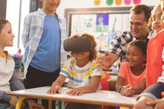 Schoolboy using virtual reality headset with his classmate and teacher. Front view of a schoolboy using virtual reality headset with his classmate and teacher at royalty free stock photography