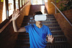 Schoolboy using virtual reality headset on staircase. At school Stock Photo