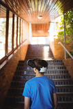 Schoolboy using virtual reality headset on staircase. At school Stock Image