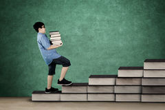 Schoolboy walking on staircase with books Stock Photography
