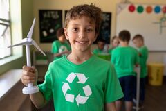 Schoolboy wearing a green t shirt with a white recycling logo on it and holding miniature wind turbi