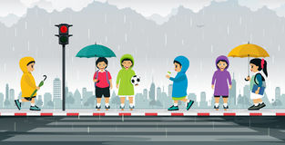 Schoolboy wearing raincoat. Schoolboy wears a raincoat and holds an umbrella to protect the rain Stock Image