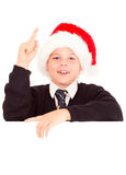 Schoolboy wearing in santa hat. Over a blank sign Stock Photo