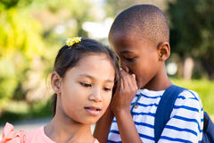Schoolboy whispering to girl at campus. Close-up of schoolboy whispering to girl at campus Royalty Free Stock Photos