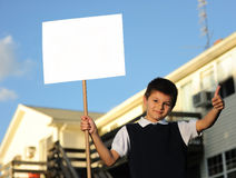 The schoolboy with the white blank. Board against the house Stock Photo
