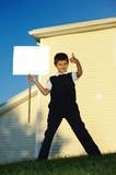 The schoolboy with the white blank. The boy costs and holds a bulletin board Royalty Free Stock Photo