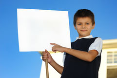 The schoolboy with the white blank. Board against the house Royalty Free Stock Photos