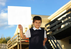 The schoolboy with the white blank. Board against the house Royalty Free Stock Image